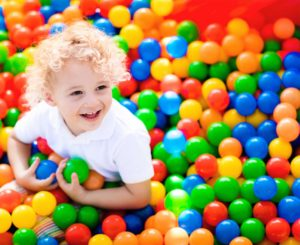 Child playing in ball pit in playground