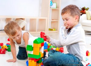 Children playing with construction set on the floor