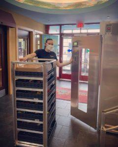 Employee pushing ZONO cart full of toys into ZONO Disinfecting & Sanitizing Cabinet