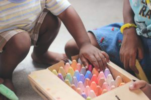 Children picking out chalk from a box