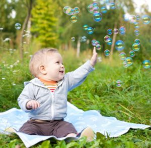 Infant playing with bubbles outside