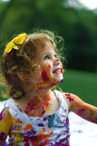 A little girl smiling with paint on her face and clothing