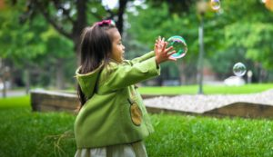 Little girl playing with bubbles outside