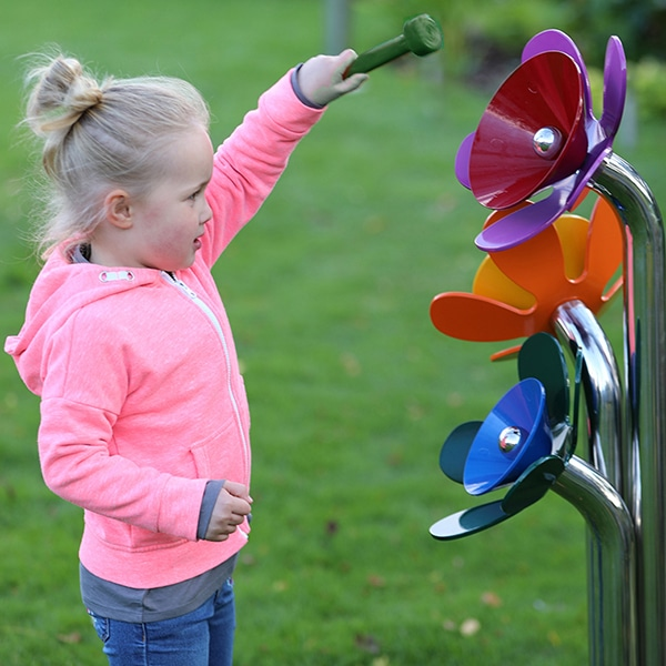 little girl playing with floral-shaped musical equipment
