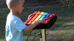 little boy playing with outdoor music instrument