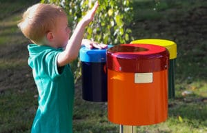 little boy playing with outdoor bongo instrument