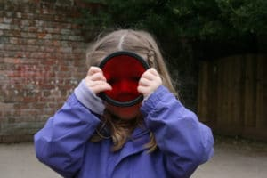 Little girl holding up red circle Poddely toy over face