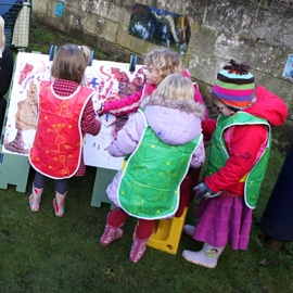 Four little girls playing with outdoor painting toy