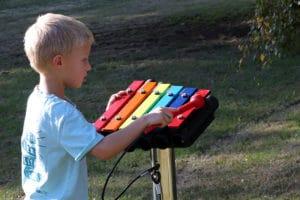 Young boy playing metallophone in Music Garden